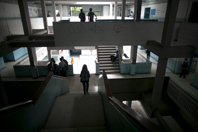 In this June 1, 2016 photo, students walk inside their public high school in Caracas, Venezuela. While the school locks its gate each morning, armed robbers still manage to infiltrate and stick up kids between classes. (Photo by Ariana Cubillos/AP Photo)