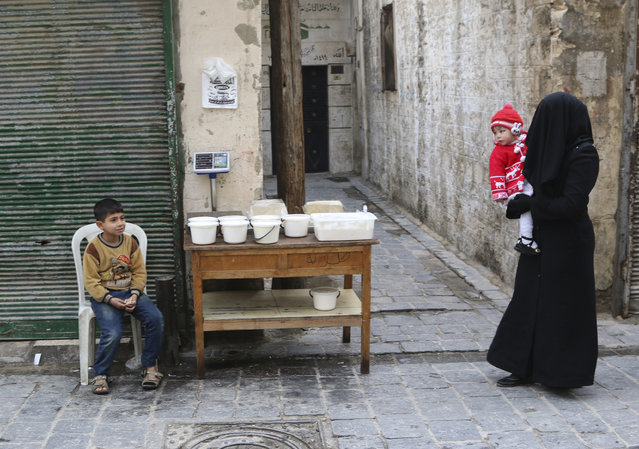 A woman carries a child as she walks past a boy selling yogurt along a street in Aleppo's Bab al-Hadeed district December 10, 2014. (Photo by Mahmoud Hebbo/Reuters)