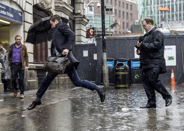 A man jumps over a puddle outside Victoria Station, as heavy rain falls,  in London, Monday June 20, 2016. Monday marks the Summer Solstice – the longest day of the year and the astronomical change of seasons when days are longest and nights are shortest in the Northern Hemisphere. (Photo by Lauren Hurley/PA Wire via AP Photo)