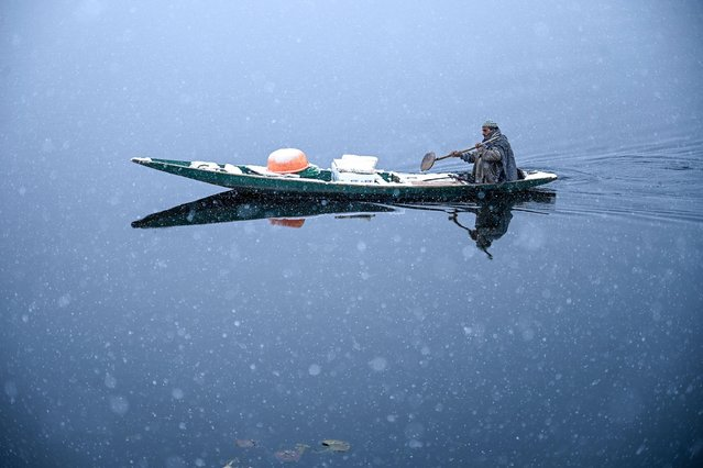 A man rides a boat in the Dal Lake during a snowfall in Srinagar on January 12, 2020. (Photo by Tauseef Mustafa/AFP Photo)