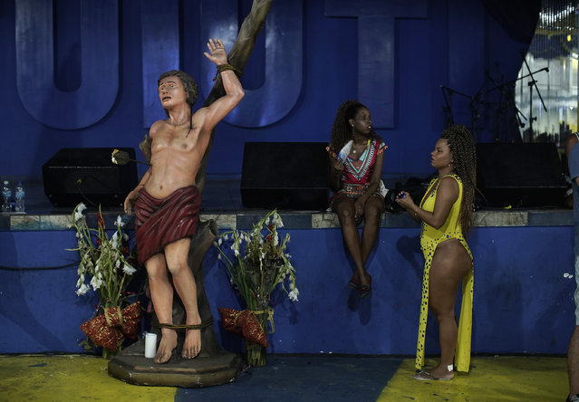 In this January 27, 2020 photo, performers wait next to a image of Saint Sebastian, patron saint of the Rio de Janeiro, for the start of the rehearsal at the Paraiso de Tuiuti samba school, in Rio de Janeiro, Brazil. The school has been a cradle of Carnival culture for people of the working-class favela near downtown Rio de Janeiro for over 60 years. (Photo by Silvia Izquierdo/AP Photo)