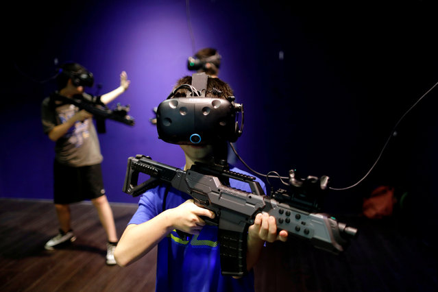 """Children wear HTC's Vive VR goggles as they play a VR game at the first Taiwanese VR theme park """"Viveland"""", in Taipei, Taiwan, August 1, 2017. (Photo by Tyrone Siu/Reuters)"""