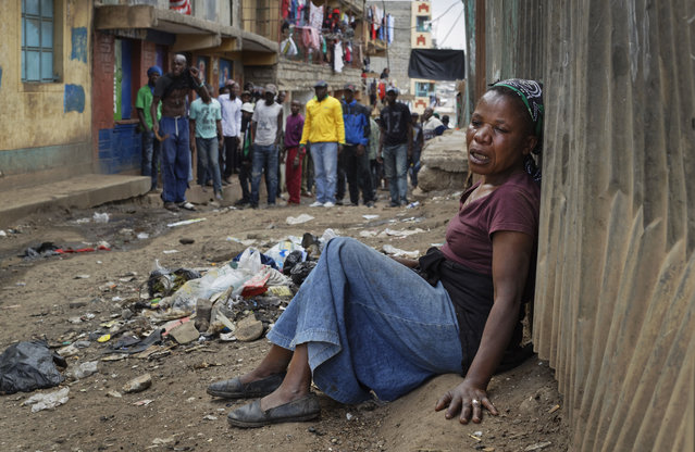 A relative wails on the floor of an alleyway near to the body of a man who had been shot in the head and who the crowd claimed had been shot by police, as the angry crowd shouts towards the police, in the Mathare slum of Nairobi, Kenya Wednesday, August 9, 2017. Kenya's election took an ominous turn on Wednesday as violent protests erupted in the capital. (Photo by Ben Curtis/AP Photo)