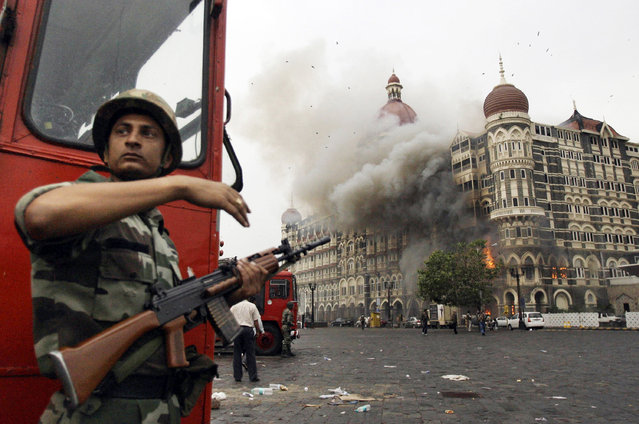 In this November 29, 2008, file photo, an Indian soldier takes cover as the Taj Mahal hotel burns during gun battle between Indian military and militants inside the hotel in Mumbai, India. A Pakistani militant leader with a $10 million bounty on his head over his alleged involvement in the 2008 Mumbai terror attacks now has a new target: A Bollywood film that imagines him being assassinated. (Photo by David Guttenfelder/AP Photo)