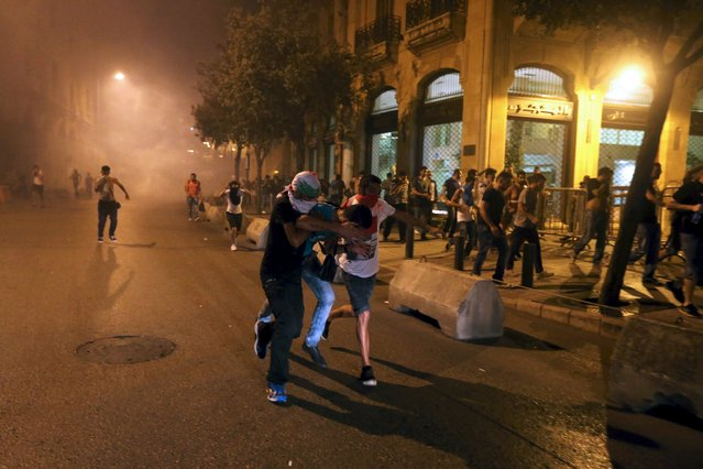Protestors run during a protest against corruption and rubbish collection problems near the government palace in Beirut, August 22, 2015. (Photo by Hasan Shaaban/Reuters)