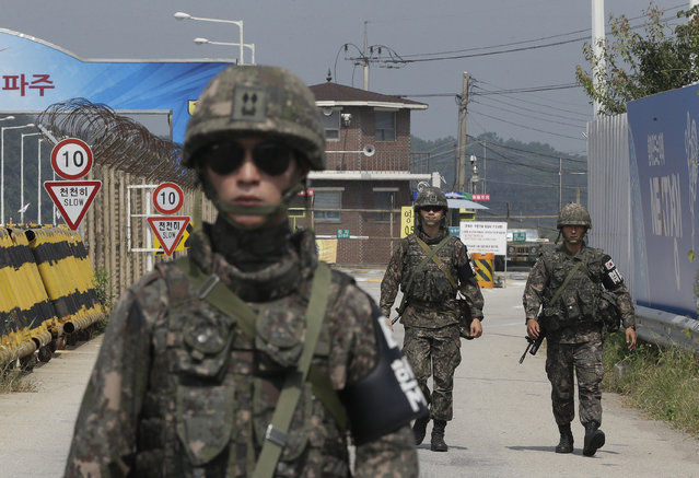 South Korean amy soldiers walk on Unification Bridge, which leads to the demilitarized zone, near the border village of Panmunjom in Paju, South Korea, Sunday, August 23, 2015. South Korean and North Korean officials have resumed the second round of their high-level talks in the border village of Panmunjom on Sunday afternoon in an effort to ease mutual tension, South Korea's presidential office said. (Photo by Ahn Young-joon/AP Photo)