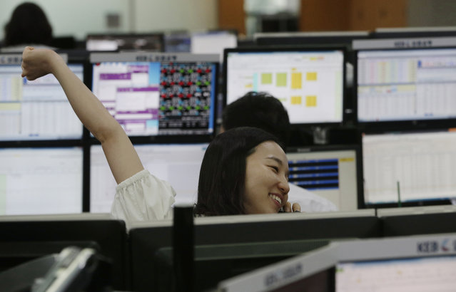 A currency trader stretches while working at the foreign exchange dealing room of the Korea Exchange Bank headquarters in Seoul, South Korea, Thursday, August 27, 2015. Asian stocks rose Thursday after Wall Street soared overnight, breaking a six-day string of losses. (Photo by Ahn Young-joon/AP Photo)