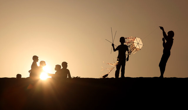 Palestinian children fly kites and sit watching the sunset n Khan Younis, a town and refugee camp in the southern Gaza Strip, Friday, February 28, 2014. (Photo by Hatem Moussa/AP Photo)
