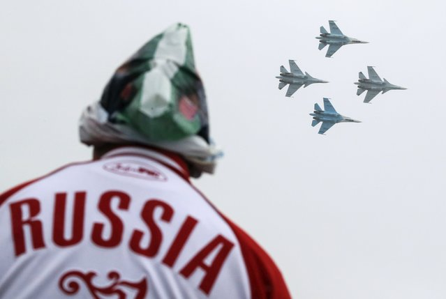 A spectator watches Sukhoi Su-30SM jet fighters of the Sokoly Rossii (Falcons of Russia) aerobatic team perform during the MAKS International Aviation and Space Salon in Zhukovsky, outside Moscow, Russia, August 29, 2015. (Photo by Maxim Shemetov/Reuters)