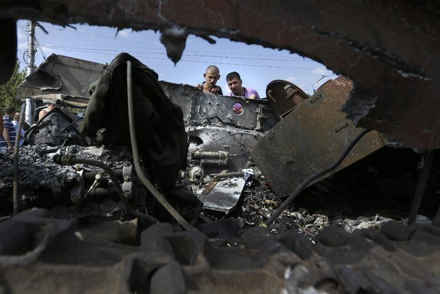 People inspect damaged heavy hardware from the Ukrainian army during an exhibition in the central square in Donetsk, eastern Ukraine, Sunday, August 24, 2014. Ukraine has retaken control of much of its eastern territory bordering Russia in the last few weeks, but fierce fighting for the rebel-held cities of Donetsk and Luhansk persists. (Photo by Sergei Grits/AP Photo)