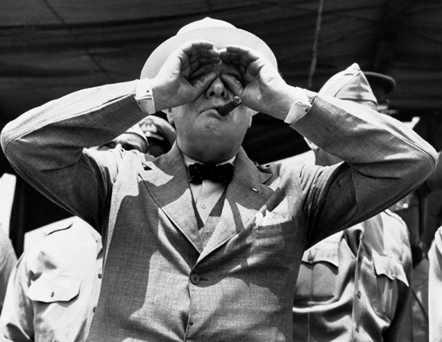 Britain's Prime Minister Winston Churchill, squinting and making binoculars of his hands as he strains to watch U.S. Army paratroops floating down from the sky, somewhere in America, on July 6, 1942, during the demonstration arranged for his benefit during the last days of his stay in America. (Photo by AP Photo)