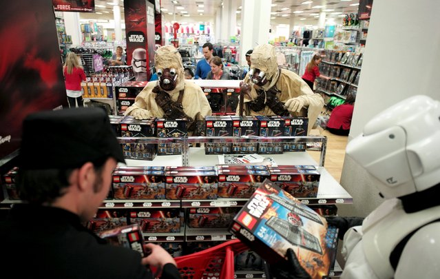 """Star Wars fans dressed as Sand People from the planet Tatooine select the new toys from the upcoming film """"Star Wars: The Force Awakens"""" just before midnight on """"Force Friday"""",September 4, 2015. (Photo by Jason Reed/Reuters)"""