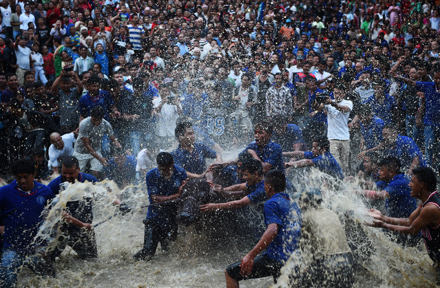 Nepali Hindu devotees splash water on a buffalo set to be sacrificed during the Hindu Dashain Festival in Bhaktapur, on the outskirts of Kathmandu, on September 29, 2017.brates the triumph of good over evil. Dashain is the longest and the most auspicious festival in the Nepalese calendar and celebrates the triumph of good over evil. (Photo by Prakash Mathema/AFP Photo)
