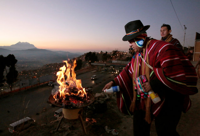 "A Bolivian Aymara man sprays alcohol to burn an offerings for the ""Pachamama"" (Mother Earth) in El Alto, Bolivia, August 1, 2016. (Photo by David Mercado/Reuters)"