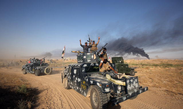 Iraqi pro-government forces advance towards the city of Fallujah on May 23, 2016, as part of a major assault to retake the city from Islamic State (IS) group. Iraqi forces, consisting of special forces, soldiers, police, militia forces and pro-government tribesmen, launched a major assault to retake Fallujah, the scene of deadly battles during the US occupation and one of the toughest targets yet in Baghdad's war on the Islamic State group. (Photo by Ahmad Al-Rubaye/AFP Photo)