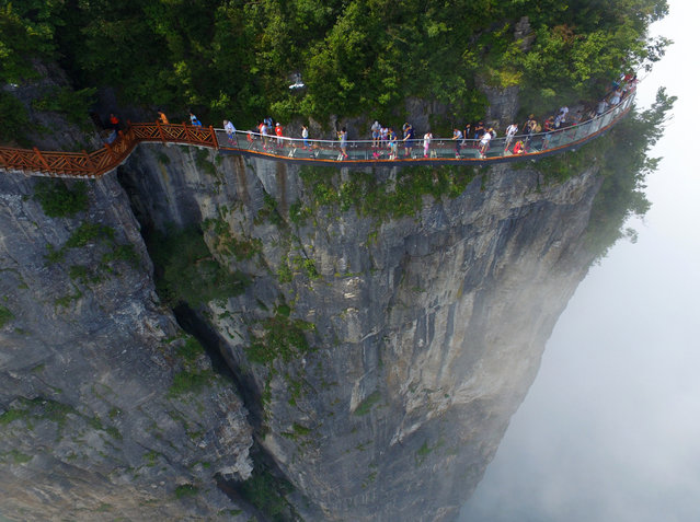 """China has opened a 100-metre-long glass skywalk stretching around a cliff on the side of the Tianmen Mountain in Hunan province. The skywalk provides a view of a 300-metre drop and overlooks Tongtian Avenue, a mountain road with 99 turns that snakes up the mountain. When translated in English, it means """"Avenue to the Sky"""". The 1.6-metre wide glass-floored skywalk has been dubbed """"Coiling Dragon Cliff"""" and is the third of its kind in the area. The area is incredibly popular with tourists and has a range of attractions including a cable car that transports people from the nearby train station to the top of the mountain. (Photo by VCG/VCG via Getty Images)"""