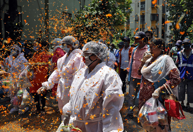 Health and municipal workers are showered with flower petals by the residents during an event to show gratitude towards the frontline warriors fighting the coronavirus disease (COVID-19) outbreak, in a residential area in Kolkata, India, May 16, 2020. (Photo by Rupak De Chowdhuri/Reuters)