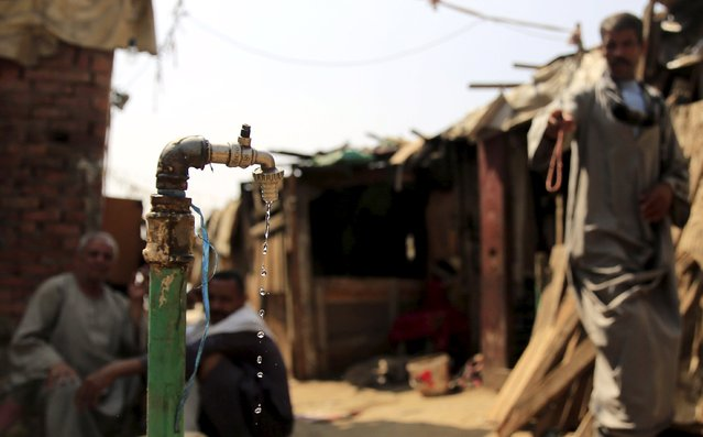 Water drips from a tap as people sit in the Eshash el-Sudan slum in the Dokki neighbourhood of Giza, south of Cairo, Egypt September 2, 2015. (Photo by Amr Abdallah Dalsh/Reuters)
