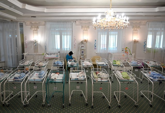 A nurse cares for newborn babies at Kiev's Venice hotel on May 15, 2020. More than 100 babies born to surrogate mothers have been stranded in Ukraine as their foreign parents cannot collect them due to border closures imposed during the coronavirus pandemic, authorities said on May 14. (Photo by Sergei Supinsky/AFP Photo)