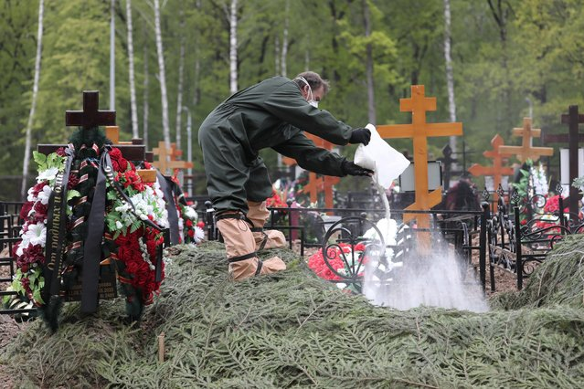 An employee wearing protective gear pours a white substance into a grave during a funeral at a cemetery amid the outbreak of the coronavirus disease in Moscow, Russia on May 26, 2020. (Photo by Sofya Sandurskaya/Moscow News Agency/Handout via Reuters)