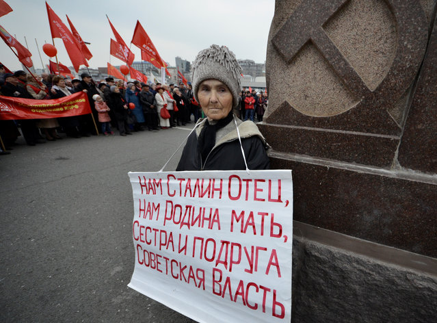 "A woman holds a placard as she takes part in a rally to mark the Red October revolution's centenary in the far eastern city of Vladivostok, Russia on November 7, 2017. The placard reads, ""Stalin is our father, homeland is our mother, Soviet power is our sister and our friend"". (Photo by Yuri Maltsev/Reuters)"