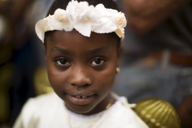 Janeli Cardenas, 8, looks at the camera during the annual procession of Our Lady of Charity, the patron saint of Cuba, on the streets of downtown Havana, September 8, 2015. (Photo by Alexandre Meneghini/Reuters)