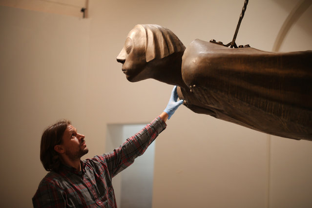 """Guy Howard-Evans inspects the final installation of Barlach's """"Hovering Angel"""" sculpture at the British Museum on October 3, 2014 in London, England. The  piece by Ernst Barlach is his memorial to those killed in the First World War and forms part of the museum's """"Germany: Memories of a Nation"""" exhibition which opens on October 16, 2014 until January 25, 2015. (Photo by Peter Macdiarmid/Getty Images)"""