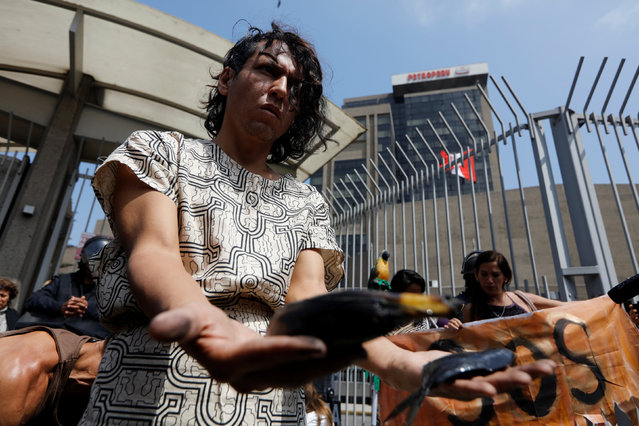 An activist takes part in a performance to protest against oil polution in the amazon jungle in front of Petroperu (Petroleos del Peru) building In Lima, Peru, August 22, 2016. (Photo by Guadalupe Pardo/Reuters)