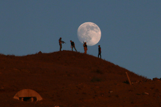 Free Syrian army fighters stand atop of a hill as the moon is seen in the background in the south of Nawa city, in Deraa Governorate, Syria August 16, 2016. (Photo by Alaa Al-Faqir/Reuters)