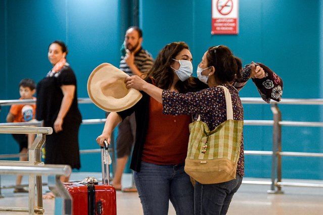 A mask-clad Tunisian woman arriving back from France embraces family members upon arrival at Tunis-Carthage International Airport in the Tunisian capital on June 27, 2020, as the North African country re-opens its land, sea, and air borders following a four-month closure due to the COVID-19 coronavirus pandemic. (Photo by Fethi Belaid/AFP Photo)