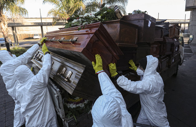 Workers collect and stack the coffins of people that have been recently cremated amid the new coronavirus pandemic at La Recoleta cemetery, amid the new coronavirus pandemic in Santiago, Chile, Tuesday, June 30, 2020. The coffins are collected and destroyed by a company specializing in organic waste. (Photo by Esteban Felix/AP Photo)