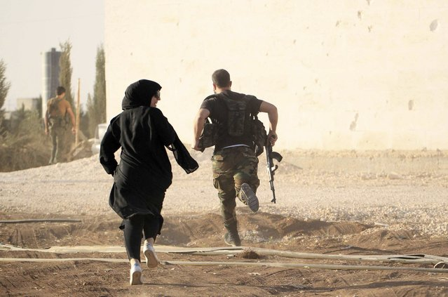 A woman reporter runs with a rebel fighter to avoid snipers at the frontline against the Islamic State fighters in Aleppo's northern countryside October 10, 2014. (Photo by Jalal Al-Mamo/Reuters)