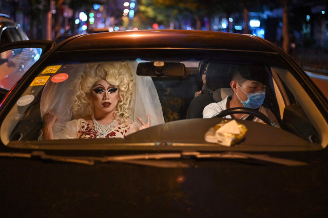 Yan Anyu or Miss Cream rides in a taxi in Shanghai on June 13, 2020, as she makes her way to a bar in the city of Shanghai to make her first presentation as a drag queen. Attitudes toward alternative lifestyles are slowly softening in China, and members of a small but growing drag community have begun to step into the spotlight. (Photo by Hector Retamal/AFP Photo)