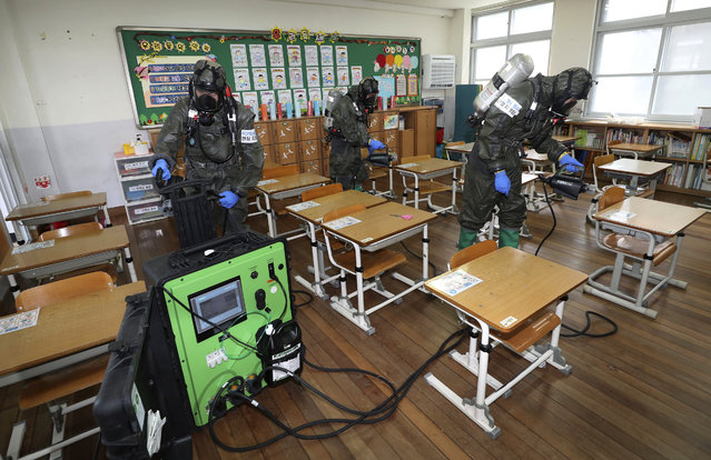 South Korean army soldiers spray disinfectant to help reduce the spread of the new coronavirus in a class at Cheondong elementary school in Daejeon, South Korea, Thursday, July 2, 2020. South Korea reported dozens of new cases as the virus continues to spread beyond the capital area and reach cities like Gwangju, which has shut schools and tightened social restrictions after dozens were found infected this week. (Photo by Kim Jun-beom/Yonhap via AP Photo)