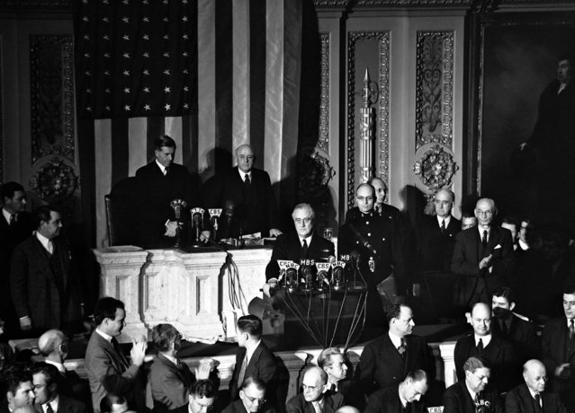 Declaring Japan guilty of a dastardly unprovoked attack, President Franklin D. Roosevelt asked Congress to declare war, December 8, 1941. Listening are Vice President Henry Wallace (left) and House Speaker Sam Rayburn. (Photo by Associated Press)