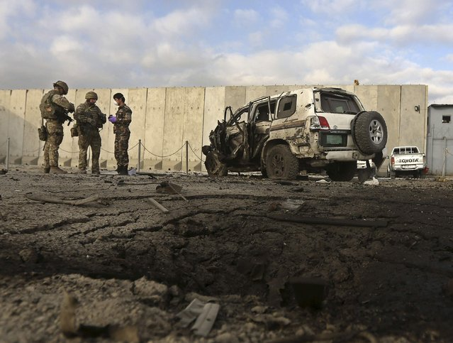 NATO troops investigate at the site of a suicide attack in Kabul October 13, 2014. A suicide car bomber rammed a foreign convoy along a major road out of Afghanistan's capital Kabul early on Monday, killing at least one person, authorities said. (Photo by Omar Sobhani/Reuters)
