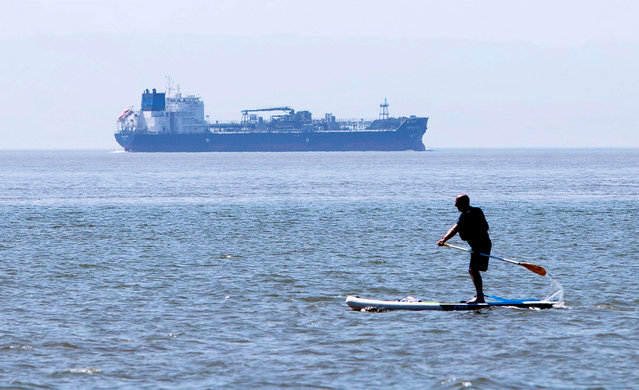 Picture shows a man paddle boarding in the shadow of a tanker ship at Barry Island, Wales on June 24, 2020 to enjoy the sunshine as temperatures rise to 30 degrees on the hottest day of the year. (Photo by Chris Fairweather/Huw Evans/Rex Features/Shutterstock)