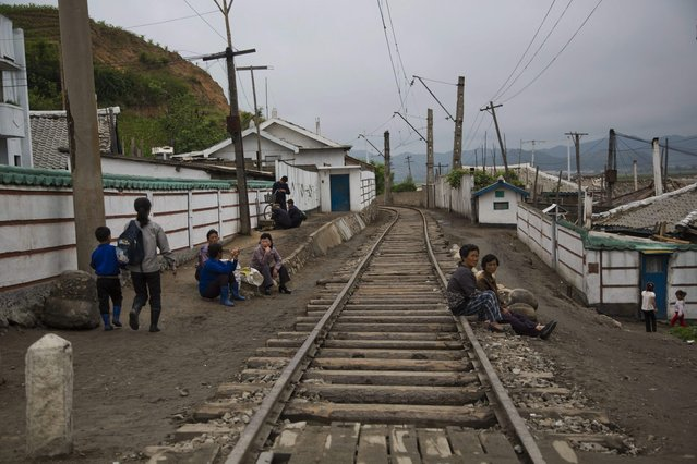 In this June 20, 2014 photo, North Korean people rest next to the railroad tracks in a town in North Korea's North Hamgyong province. (Photo by David Guttenfelder/AP Photo)