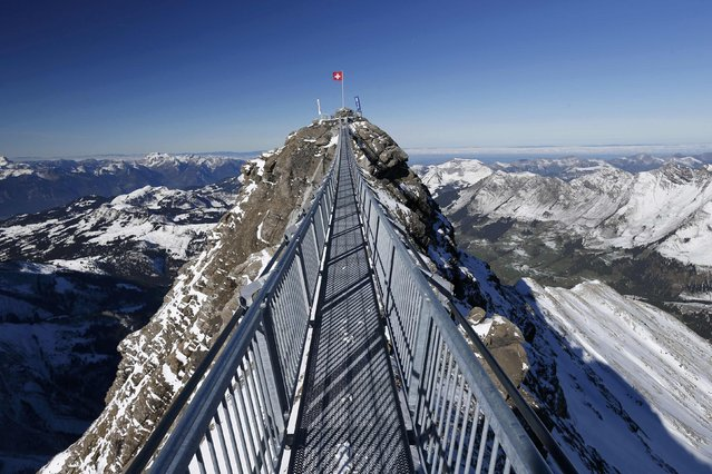 """A Swiss national flag flies at one end of the """"Peak Walk"""" bridge during a media preview, at the Glacier 3000 in Les Diablerets October 24, 2014. (Photo by Denis Balibouse/Reuters)"""