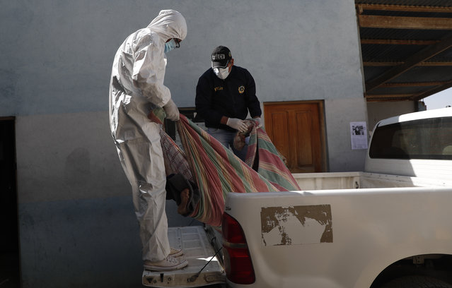 Police in protective gear amid the COVID-19 pandemic lift a body with the deceased person's own bedding, as they arrive at the morgue of the General Hospital in La Paz, Bolivia, Wednesday, August 5, 2020. Police routinely carry out the removal of corpses from streets and homes, and now about 80% are suspected of having COVID-19, according to the director of the Special Force to Fight Crime (FELCC), Colonel Ivan Rojas. (Photo by Juan Karita/AP Photo)