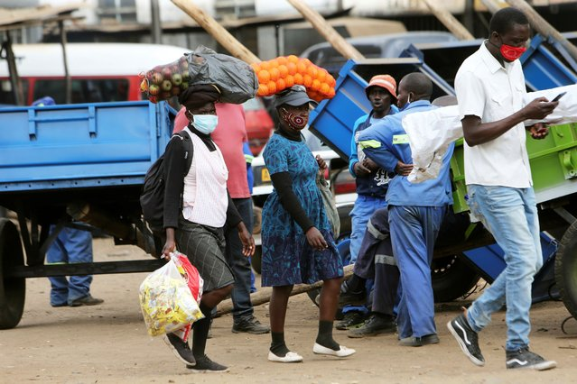 Women carry fruits on their heads after shopping at Mbare vegetable market in Harare, Wednesday, August 5, 2020. Zimbabwe's Information Minister has announced that the market place is now a hot spot for the spread of Covid -19. (Photo by Tsvangirayi Mukwazhi/AP Photo)