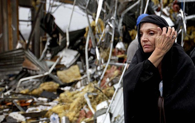 Pam Parker sifts through debris while looking for any personal belongings in the area where she was sitting at her desk when a tornado struck the Daiki plant, a metal fabrication company where she works in accounts payable in Adairsville. (Photo by David Goldman/Associated Press)