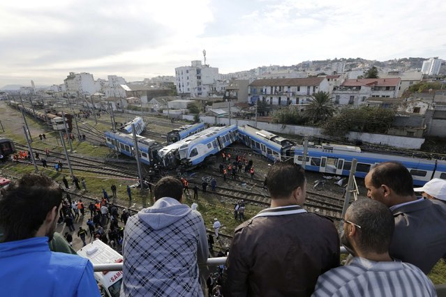 Onlookers watch from a bridge as rescue workers gather beside derailed coaches of a passenger train in Algiers November 5, 2014. According to local media, 52 passengers were injured on Wednesday after the train they were travelling on derailed. (Photo by Louafi Larbi/Reuters)