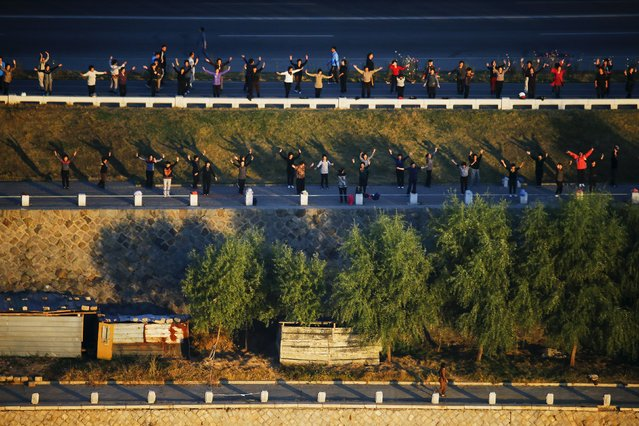 People exercise on banks of Taedong River in Pyongyang, North Korea, early October 9, 2015. (Photo by Damir Sagolj/Reuters)