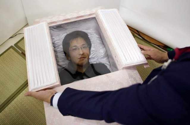 Noriaki Iwashima looks out of a coffin during an end-of-life seminar held by Japan's largest retailer Aeon Co in Tokyo October 24, 2014. (Photo by Toru Hanai/Reuters)