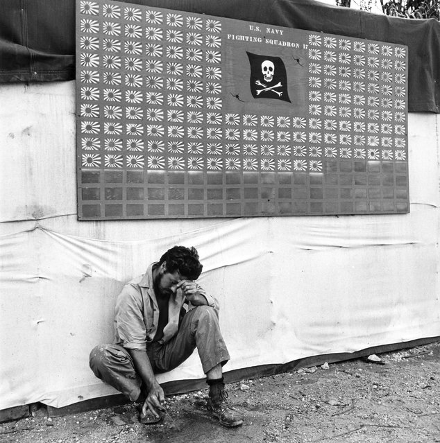 """Tired member of VF-17 pauses under the squadron scoreboard at Bouganville"", February 1944. (Photo by Charles Fenno Jacobs)"