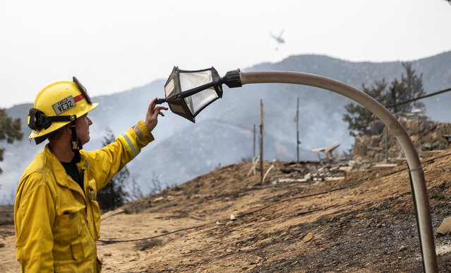 Fire engineer Paul Kahler examines a melted lamp-post destroyed by the El Dorado wildfire in California on September 7, 2020. (Photo by Cindy Yamanaka/AP Photo)