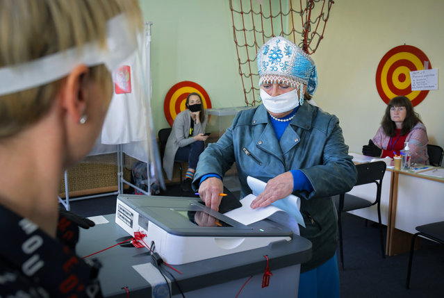 A woman wearing a face mask to protect against coronavirus infection casts her ballot at a poling station during Leningrad region's governor and municipal elections in Luppolovo village, outside St.Petersburg, Russia, Sunday, September 13, 2020. Leningrad region is the territory surrounding St. Petersburg. The elections are held to choose governors and legislators in about half of Russia's regions. (Photo by Dmitri Lovetsky/AP Photo)