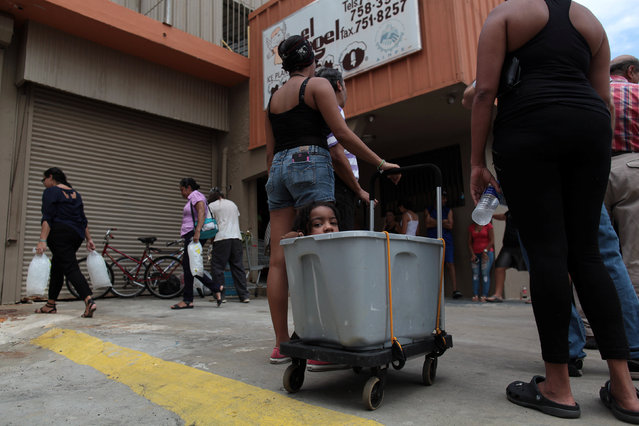 A child sits inside a cart as people wait to buy ice during a power outage after a fire at an energy plant knocked out electricity for the bulk of the island, in San Juan, Puerto Rico, September 22, 2016. (Photo by Alvin Baez/Reuters)