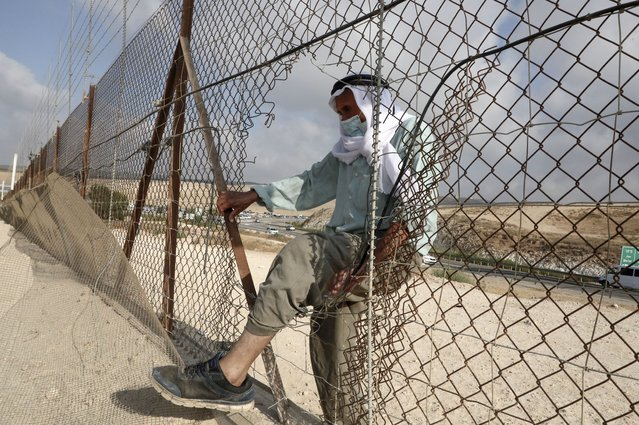 A Palestinian man enters illegally from a breach in a barrier fence into Israeli territory from the village of al-Dahriya, south the occupied West Bank town of Hebron, on August 21, 2020. (Photo by Hazem Bader/AFP Photo)